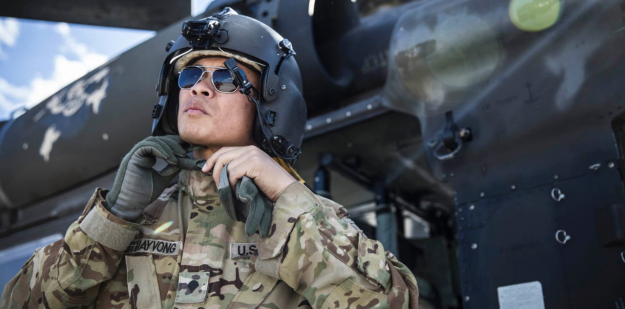 Soldier standing in front of a AH-64 Apache helicopter
