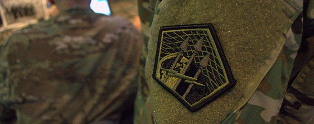 A Soldier wears the insignia of Army Cyber Command.