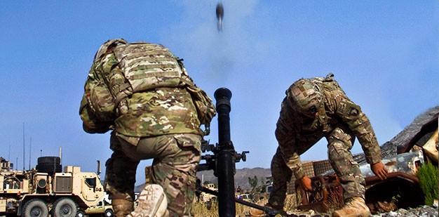Soldiers firing a mortar.