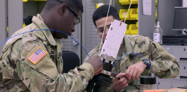U.S. Army Soldier inspects network communications wires