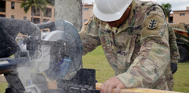 U.S. Army Soldier nails a ceiling beam in place