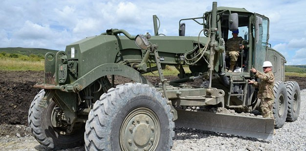 A U.S. Army Soldier directs a construction equipment operator as he moves sand with a bucket loader