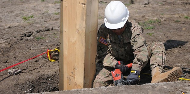 Soldier drilling into the foundation of a multipurpose building being built.