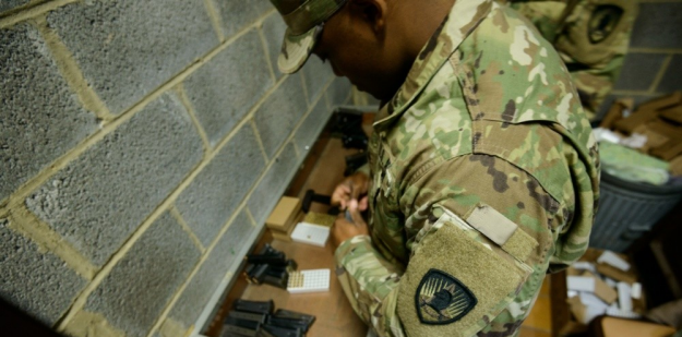 Soldier inserting bullets in a magazine.