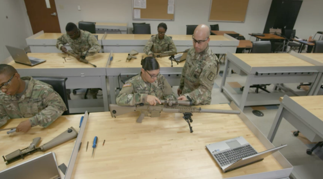 Small-arms/artillery repairmen demonstrate proper loading of a weapon