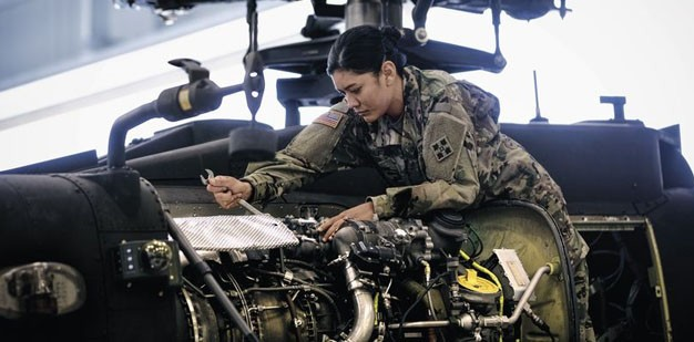 Soldier repairing a Apache helicopter inside a hangar.
