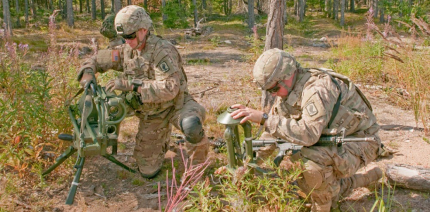 Soldiers work to mount a weapon to a vehicle