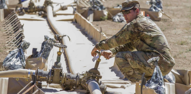 Soldier closing a Fuel System Supply Point valve.