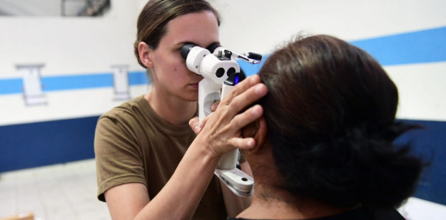 Army AMEDD optometrist examining patient