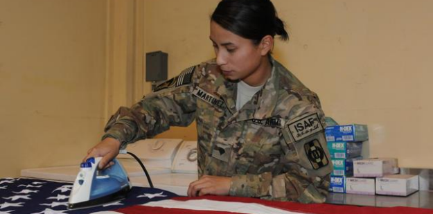 U.S. Army Soldier irons a United States flag