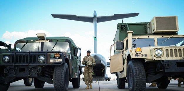 Soldier preparing to load high-mobility multipurpose wheeled vehicles, known as Humvees.