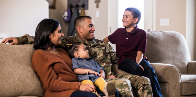 Soldier sitting on a couch with his family.