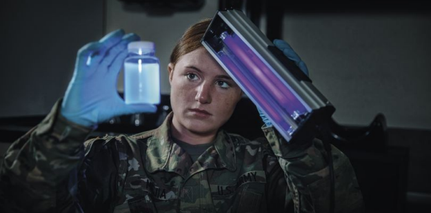 Soldier wearing OCP inside of medical facility holding a black light and a jar.
