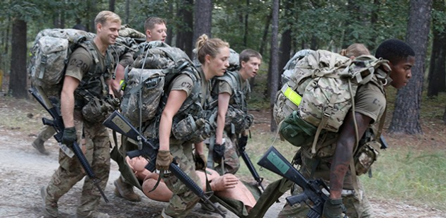 US Soldiers carrying a fake injured dummy in training as a team