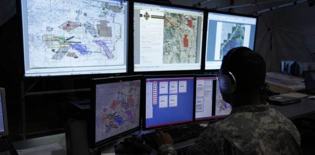 Intelligence soldier looking at multiple computer screens