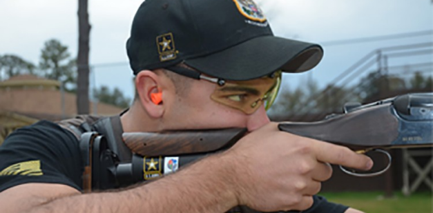 A Soldier aims down the sights of a shotgun.