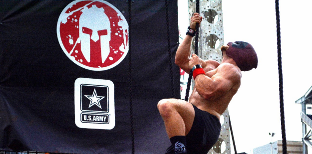 Spartan race contestant rope climbing