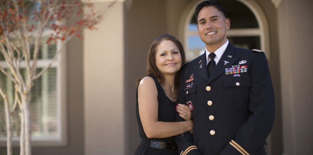 Soldier wearing dress blues standing with parent outside of house during the day.