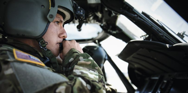 Soldier sitting in cockpit of a Blackhawk helicopter during the daytime.