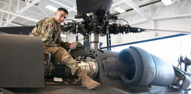Soldier repairing a Apache helicopter inside a hangar during the daytime.