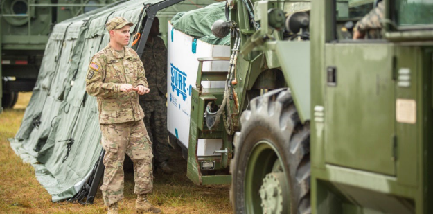 Soldier guiding an All Terrain Lifter, Army System (ATLAS) that is picking up laundry bags for a Laundry Advanced System (LADS).