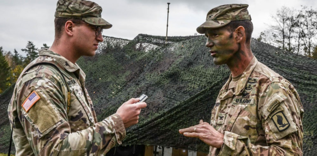 A public affairs officer conducts an interview in the field