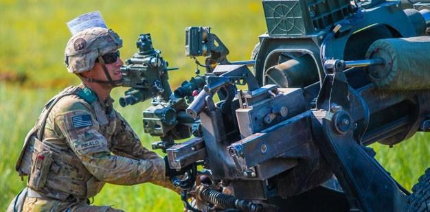 Soldier preparing a M119A3 Howitzer.
