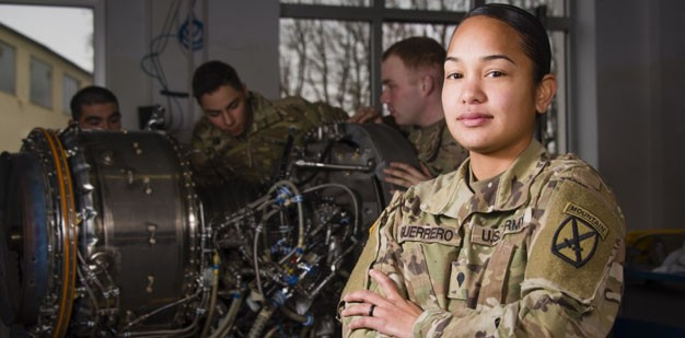 Army soldier working on aircraft engine