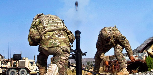 Soldiers firing a mortar.