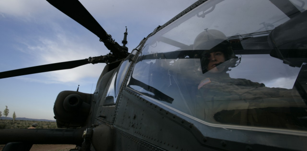 Soldier in cockpit of Apache helicopter.